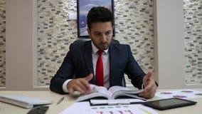 Hombre de negocios Reading Documents con los gráficos almacen de video