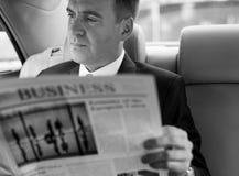 Hombre de negocios Reading Newspaper Car dentro Imagenes de archivo