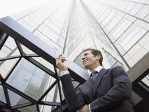 Hombre de negocios Reading SMS en el teléfono móvil contra el edificio de oficinas Imagen de archivo libre de regalías