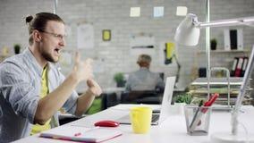 Hombre de negocios realizado productivo que inclina el trabajo de oficina detrás de acabado en el ordenador portátil, encargado e almacen de video