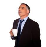 Hombre de negocios reflexivo con una taza blanca Fotos de archivo