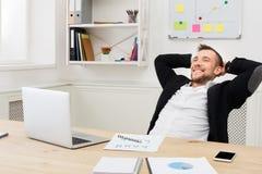 Hombre de negocios relajado joven con el ordenador portátil en oficina blanca moderna fotos de archivo libres de regalías