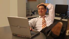 Hombre de negocios relajado usando el ordenador portátil en oficina metrajes