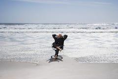 Hombre de negocios Relaxing On Chair en la playa Fotografía de archivo libre de regalías