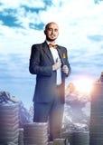 Hombre de negocios rico alegre en un traje con un manojo de dinero Fotos de archivo libres de regalías