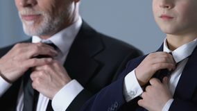 Hombre de negocios rico y su hijo en los trajes que ajustan lazos juntos, valores familiares almacen de video