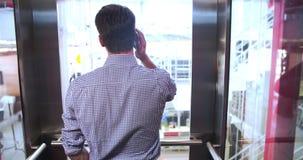 Hombre de negocios Riding Elevator And que habla en el teléfono móvil almacen de metraje de vídeo