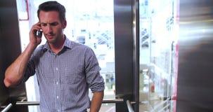 Hombre de negocios Riding Elevator And que habla en el teléfono móvil metrajes