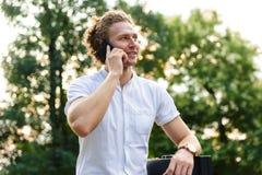 Hombre de negocios rizado contento con la cartera que habla por smartphone fotos de archivo