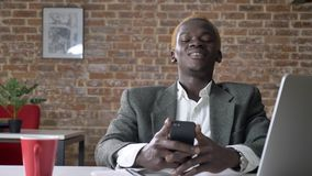 Hombre de negocios rubio afroamericano joven que manda un SMS en el teléfono y que se sienta en trabajador moderno de la oficina, almacen de video