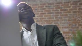 Hombre de negocios rubio feliz africano joven que habla en el teléfono y que se sienta en oficina moderna, la risa y la sonrisa almacen de video
