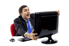 Hombre de negocios salido delante de un monitor de computadora Imagenes de archivo