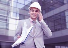 Hombre de negocios satisfecho con los papeles que habla en el teléfono foto de archivo libre de regalías