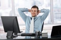 Hombre de negocios satisfecho que sonríe en el escritorio Fotografía de archivo libre de regalías
