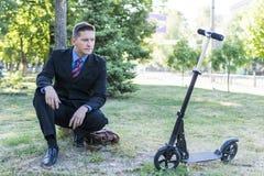 Hombre de negocios sentado por el árbol Foto de archivo