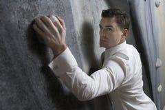 Hombre de negocios serio Climbing Indoor Wall foto de archivo libre de regalías