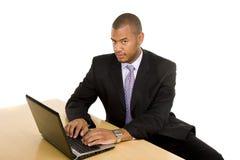 Hombre de negocios serio en el escritorio que trabaja en el ordenador portátil imagenes de archivo