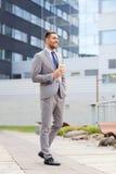 Hombre de negocios serio joven con la taza de papel al aire libre Fotos de archivo libres de regalías