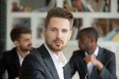Hombre de negocios serio joven que mira la cámara en la reunión, headshot foto de archivo libre de regalías