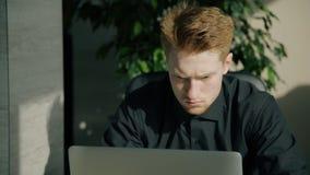 Hombre de negocios serio joven que trabaja con el ordenador portátil que se sienta en la tabla en oficina brillante almacen de metraje de vídeo