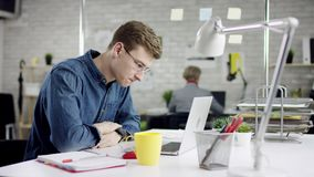 Hombre de negocios serio productivo que inclina el trabajo de oficina detrás de acabado en el ordenador portátil, encargado efica metrajes