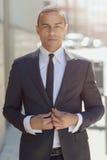 Hombre de negocios serio que ajusta su chaqueta Foto de archivo