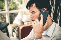 Hombre de negocios serio que hace llamada en su teléfono móvil fotos de archivo