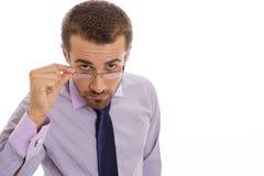 Hombre de negocios serio que mira sobre las lentes Foto de archivo