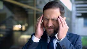 Hombre de negocios serio que sufre de la jaqueca, desorden del dolor de cabeza, síntomas imagen de archivo libre de regalías