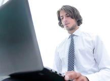 Hombre de negocios serio que trabaja en el ordenador portátil fotos de archivo