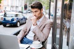 Hombre de negocios serio usando el ordenador portátil moderno en cafetería Fotos de archivo