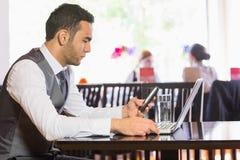 Hombre de negocios serio usando el teléfono mientras que trabaja en el ordenador portátil Imagenes de archivo