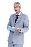 Hombre de negocios serio usando la PC de la tableta que mira lejos Imagen de archivo
