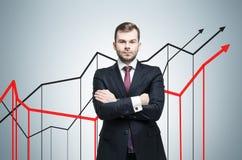 Hombre de negocios serio y tres gráficos cada vez mayor en la pared gris Foto de archivo libre de regalías