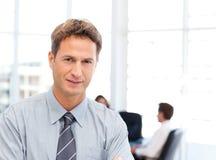 Hombre de negocios severo delante de su trabajo en equipo foto de archivo