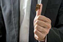 Hombre de negocios Showing Butterfly Insect en el pulgar Foto de archivo