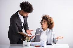 Hombre de negocios Showing Mistake To su colega femenino imágenes de archivo libres de regalías