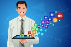 Hombre de negocios Showing Multimedia Icons de su tableta Imagen de archivo libre de regalías