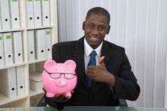 Hombre de negocios Showing Thumb Up con Piggybank Imagenes de archivo