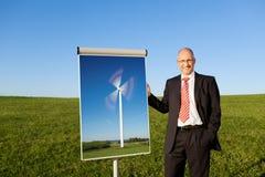 Hombre de negocios Showing Windmill Project en Flipchart en el campo herboso fotos de archivo libres de regalías