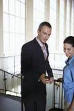 Hombre de negocios Showing Woman Cellphone en aeropuerto imagen de archivo