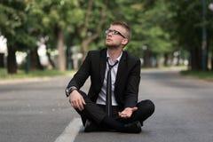 Hombre de negocios Sitting On Asphalt Begs For Money Foto de archivo libre de regalías
