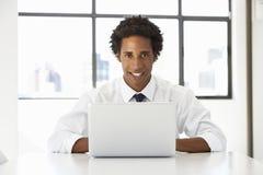 Hombre de negocios Sitting At Desk en oficina usando el ordenador portátil Imagen de archivo libre de regalías