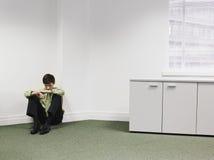 Hombre de negocios Sitting On Floor en esquina en la oficina Foto de archivo libre de regalías