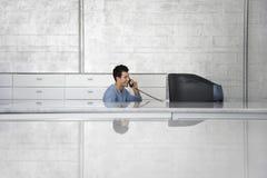 Hombre de negocios Sitting In Front Of Computer Using Telephone Imagenes de archivo