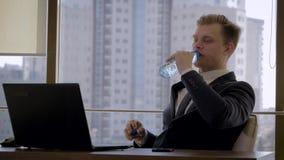 Hombre de negocios Sitting At Workplace por la ventana en oficina y agua potable almacen de video