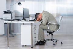 Hombre de negocios Sleeping On Desk en oficina fotos de archivo