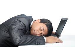 Hombre de negocios Sleeping sobre el ordenador portátil imagen de archivo