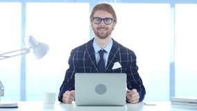 Hombre de negocios Smiling Toward Camera del pelirrojo mientras que trabaja en el ordenador portátil Fotos de archivo libres de regalías