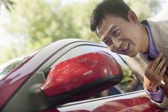 Hombre de negocios Smiling y lazo del ajuste en espejo de coche Imagen de archivo